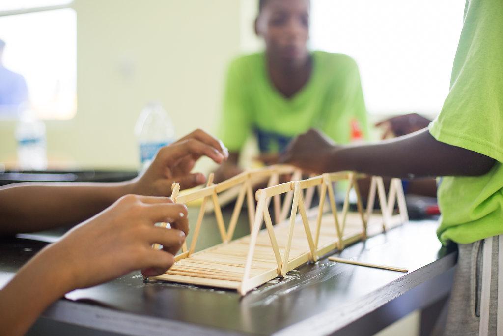 Students building bridge with popsicle sticks